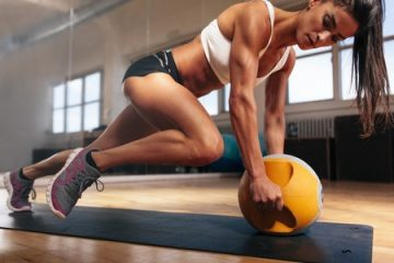 43852716 - muscular woman doing intense core workout in gym. strong female doing core exercise on fitness mat with kettlebell in health club.